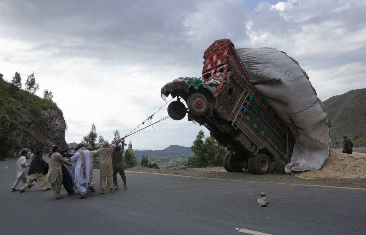 pakistani-men-in-islamabad-try-to-right-a-truck-transporting-wheat-straw